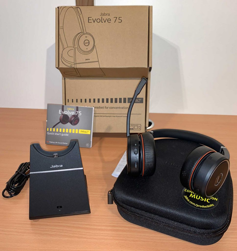 Image showing contents of box of Jabra Evolve 75. Charging docks, documentation, headset case and headset itself.