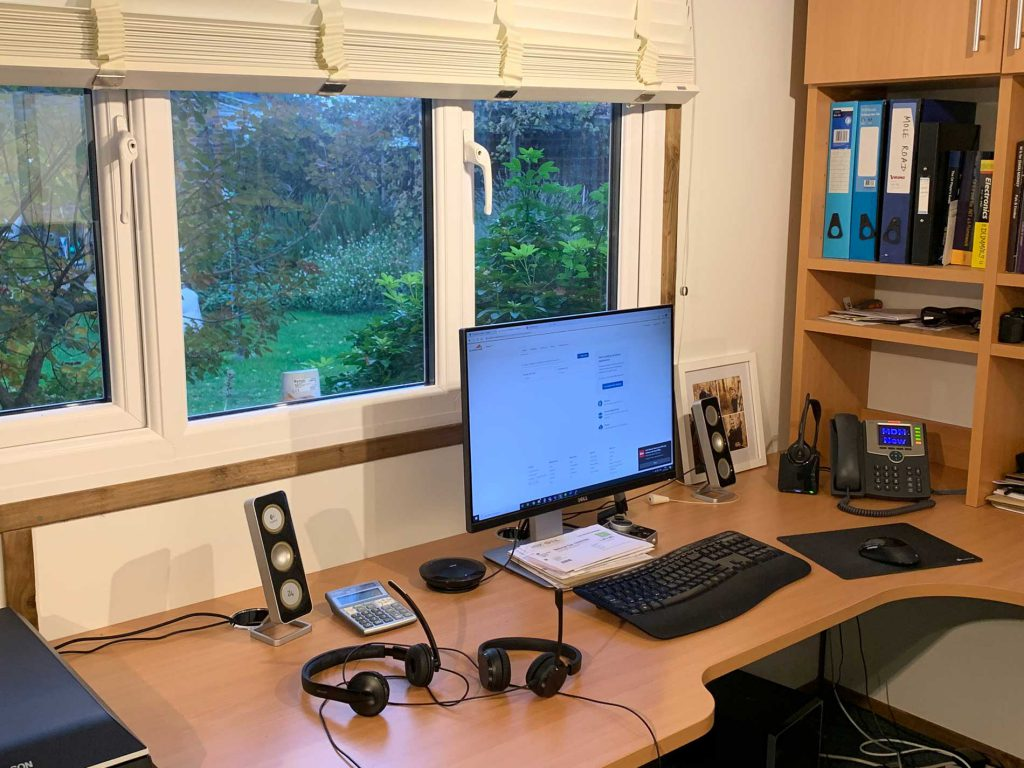 Image of office desk covered in wired headsets
